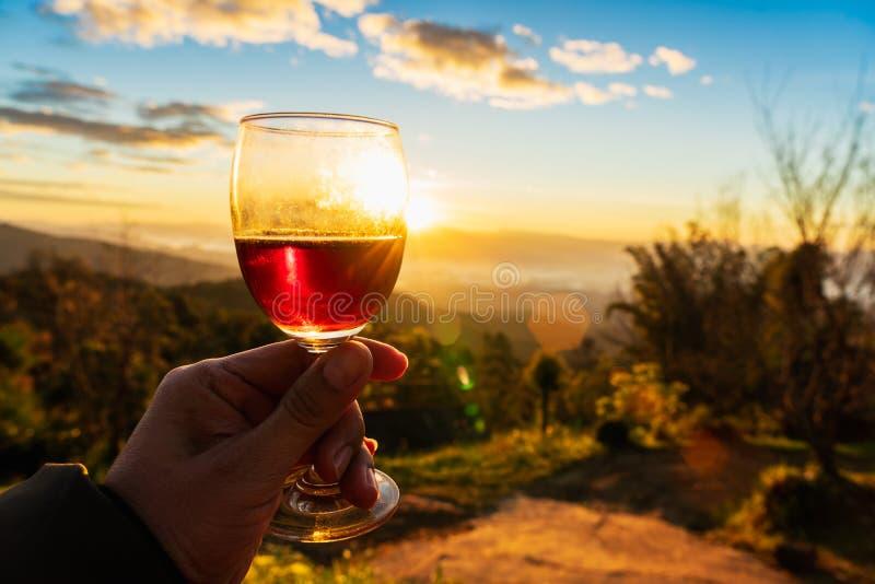Manhand som rymmer exponeringsglas av vin på solnedgångbakgrund arkivbilder