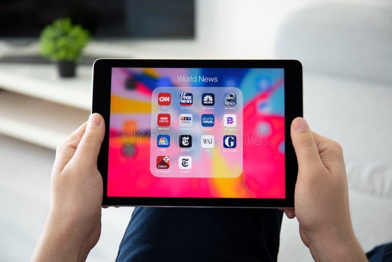 Manhand som rymmer iPad pro- med populära nyheternaapplikationer arkivfoto