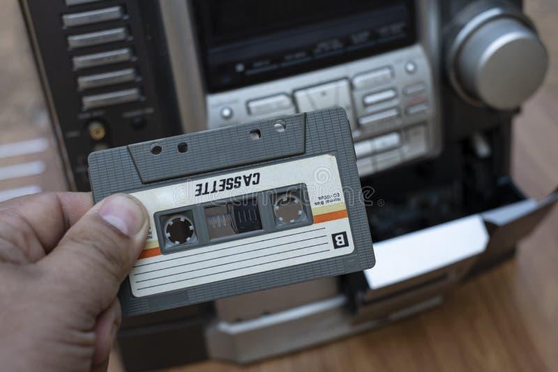 Manhand som sätter kassetten in i den gammalmodiga ljudbandspelaren på skrivbordträbakgrund royaltyfri fotografi