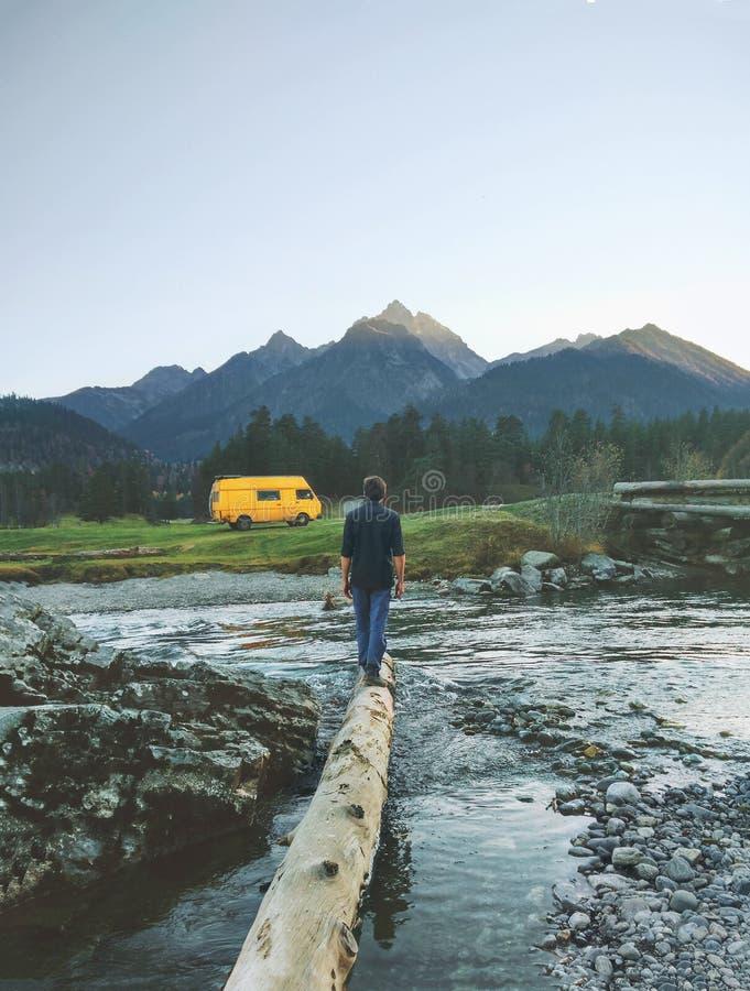 Manhandelsresande med den gula skåpbilen som campar i berg arkivbild