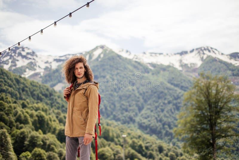 Manhandelsresande med rött koppla av för ryggsäck som är utomhus- med steniga berg på bakgrund royaltyfria bilder