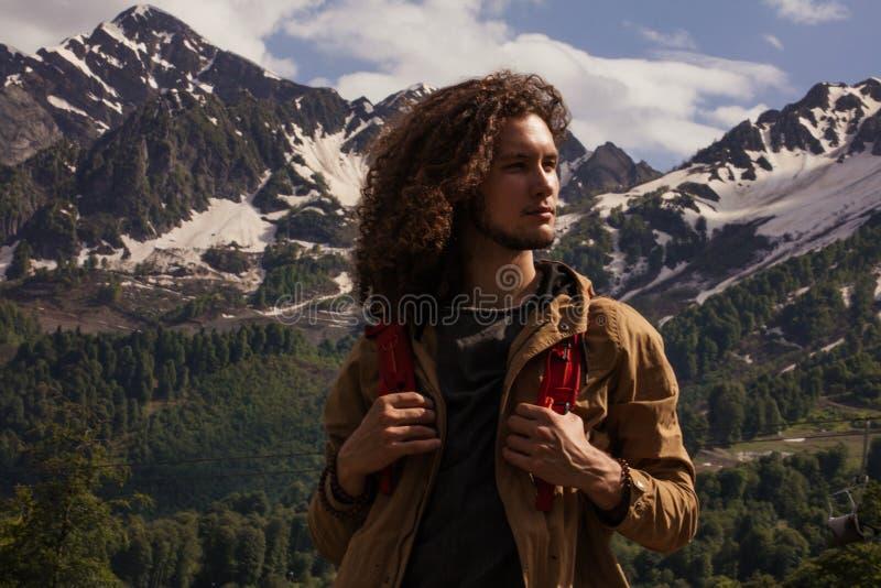 Manhandelsresande med rött koppla av för ryggsäck som är utomhus- med steniga berg på bakgrund royaltyfri fotografi