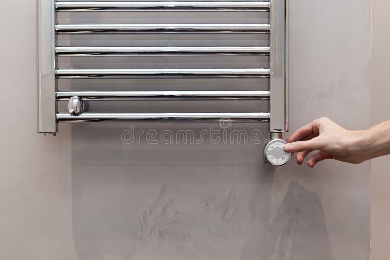 Manhanden reglerar temperaturen i den upphettade handdukstången i badrum fotografering för bildbyråer
