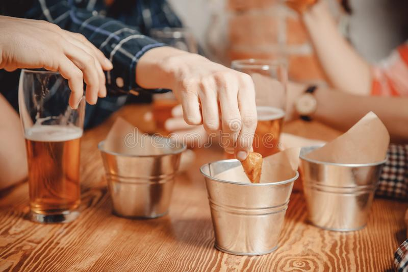 Manhanden tar mellanmålsmällare, krutonger med sås och drinköl i barstång på trätabellen royaltyfri foto