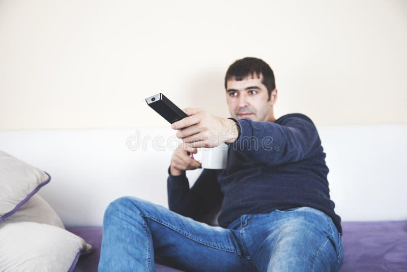 Manhandfjärrkontroll på soffan arkivfoto