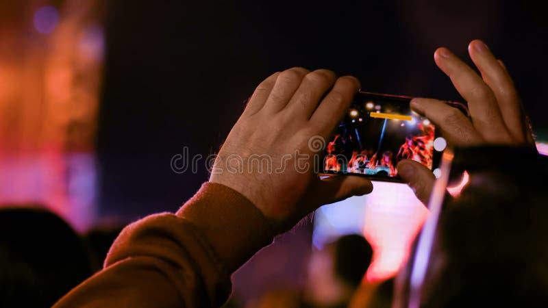 Manhandkontur som antecknar videoen av konserten f?r levande musik med smartphonen arkivfoto