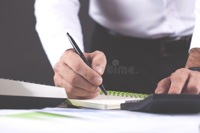 Manhandräknemaskin och notepad i regeringsställning arkivbilder
