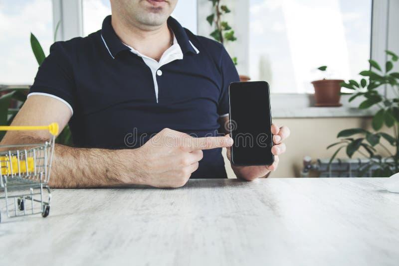 Manhandtelefon med korgen royaltyfri bild
