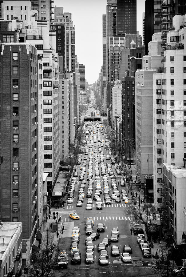 Manhattan from above. Busy street of Manhattan, New York City, in black and white, filled with cars stuck in traffic jams and yellow cabs as small colorful stock photos