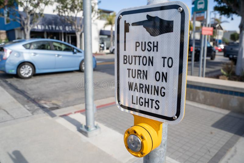 Manhattan Beach, California - Sign instructs pedestrians to push button to turn on the warning lights for cars, to royalty free stock images