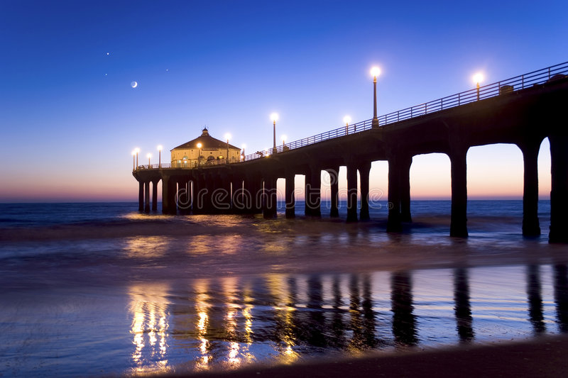 Manhattan Beach Pier at Twilight. Manhattan Beach California Pier at twilight. Moon and a few stars visible in the background. Pier lights reflecting on the sand