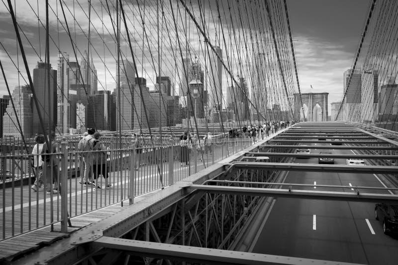 People crossing Manhattan Bridge in black and white. royalty free stock photo