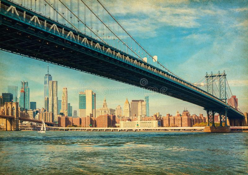 The Manhattan Bridge with Manhattan in the background at the day-time, New York City, United States. Photo in retro style. Added p. Aper texture royalty free stock photos