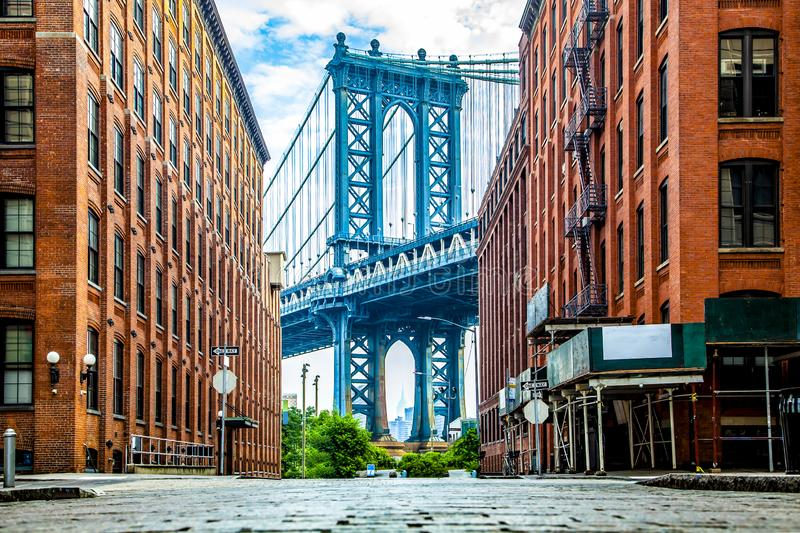Manhattan Bridge between Manhattan and Brooklyn over East River seen from a narrow alley enclosed by two brick buildings on a royalty free stock images