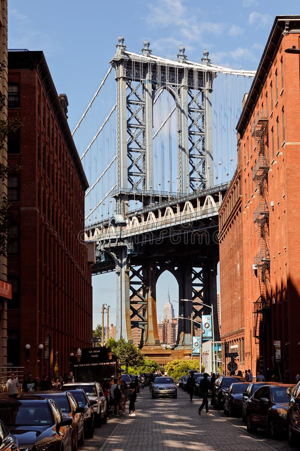 Manhattan Bridge seen from Dumbo, NYC. NEW YORK, USA - Sep 22, 2017: Manhattan Bridge with the Empire State building and brick wall buildings viewed from Dumbo royalty free stock images