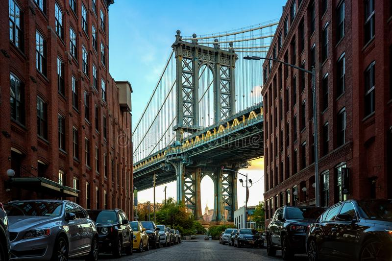 Manhattan bridge seen from a narrow alley enclosed by two brick buildings stock photo
