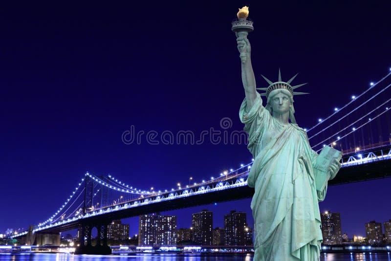 Manhattan bro och statyn av frihet på natten arkivfoton