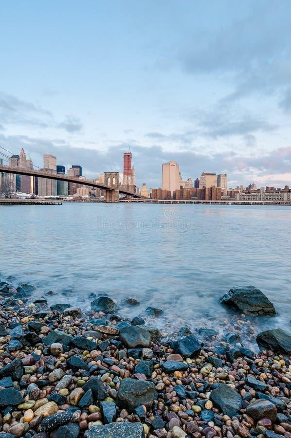 Manhattan horisont från Pebble Beach i Brooklyn, Förenta staterna royaltyfri bild