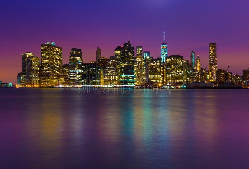 Manhattan horisont på natten med kulöra reflexioner i vatten royaltyfria bilder