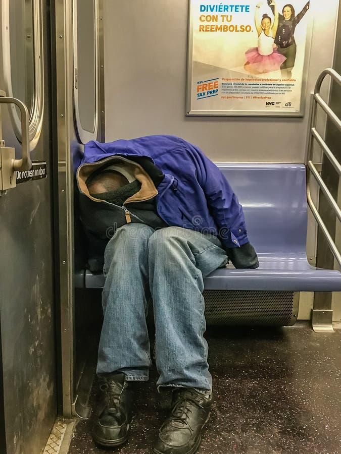 Manhattan, NY US - 26. Februar 2018 Obdachloser schläft in einem U-Bahnauto lizenzfreies stockfoto