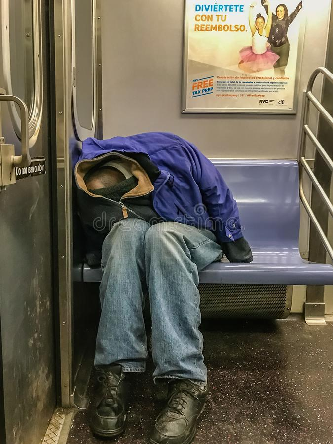 Manhattan NY USA - Februari 26, 2018 sover den hemlösa personen i en gångtunnelbil royaltyfri foto