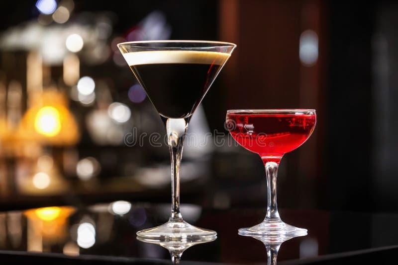 Manhattan och espressococtailar i eleganta exponeringsglas på färgrikt arkivbild