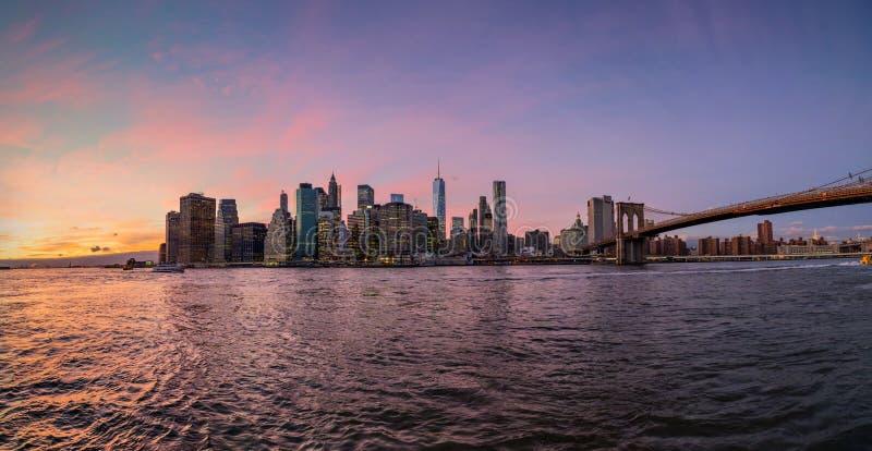 Manhattan panorama under solnedgång från den Brooklyn bron parkerar arkivfoton