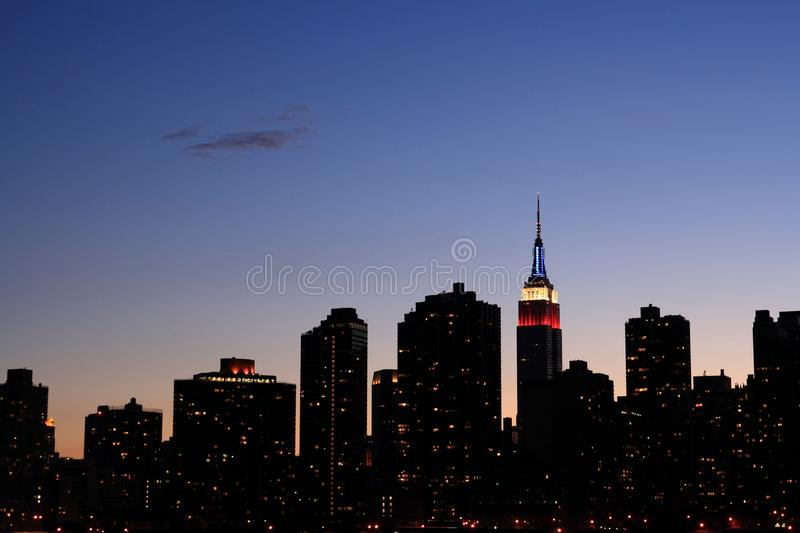Manhattan Skyline. Magic hour of Manhattan Skyline, Empire State building lit red, white, and blue royalty free stock photography