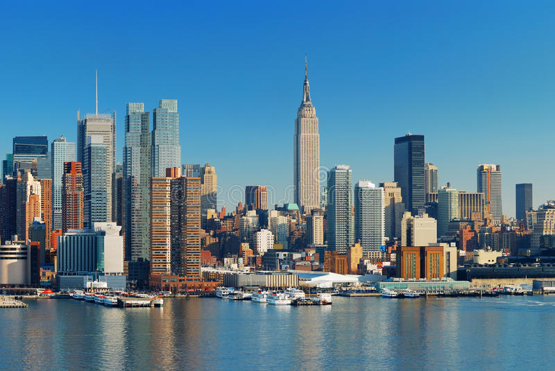 Manhattan Skyline. With Empire State Building, New York City over Hudson River with boat and pier royalty free stock image