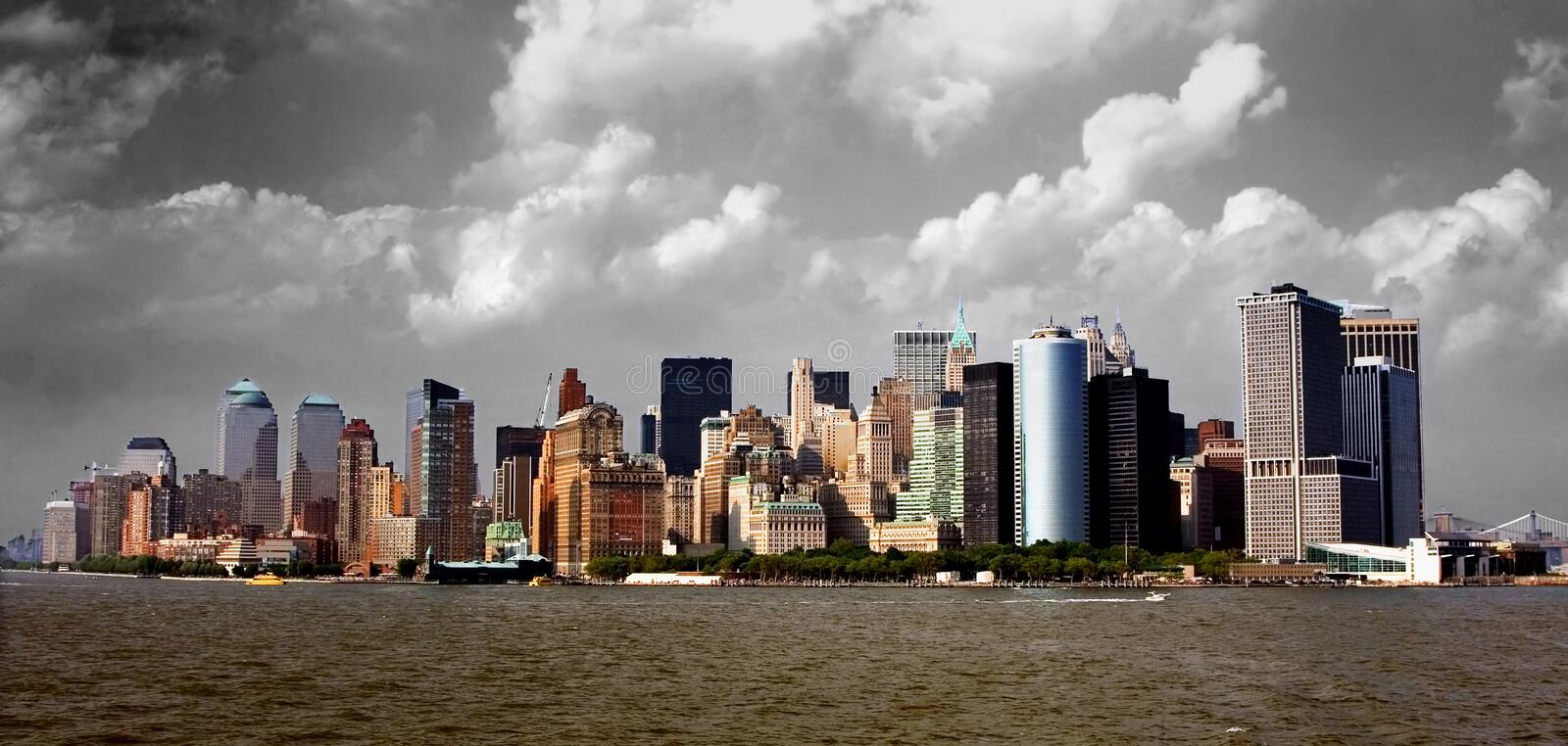 Manhattan Skyline. Dramatic view of the Lower Manhattan skyline as seen from the south. In front one can see Battery Park, with the buildings of New York's royalty free stock images