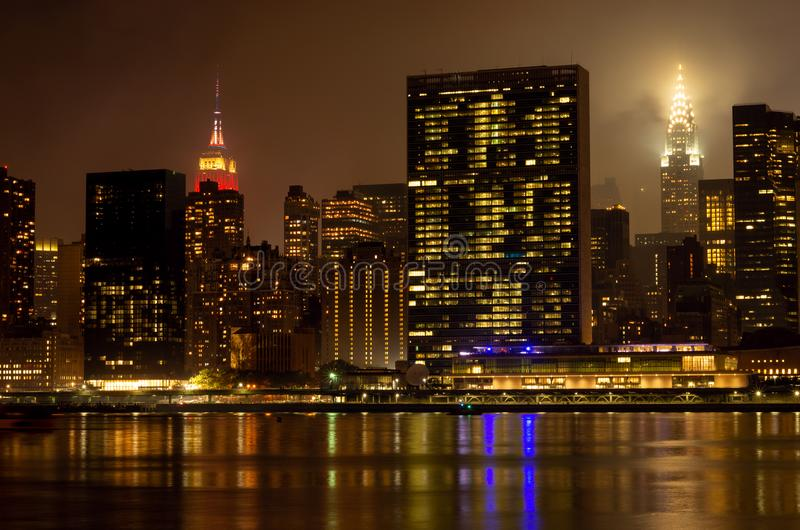 Manhattan skyline at night with reflections, NYC, USA. royalty free stock photography