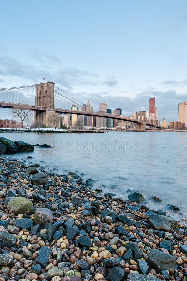 Manhattan Skyline from Pebble Beach in Brooklyn, United States. Manhattan Skyline sunrise as seen from Pebble Beach in Brooklyn, New York, United States of royalty free stock image