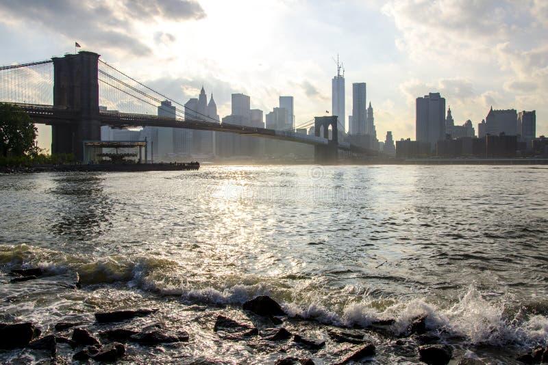 Manhattan-Skyline und Brooklyn-Brücke East River Wellen New York City stockbild