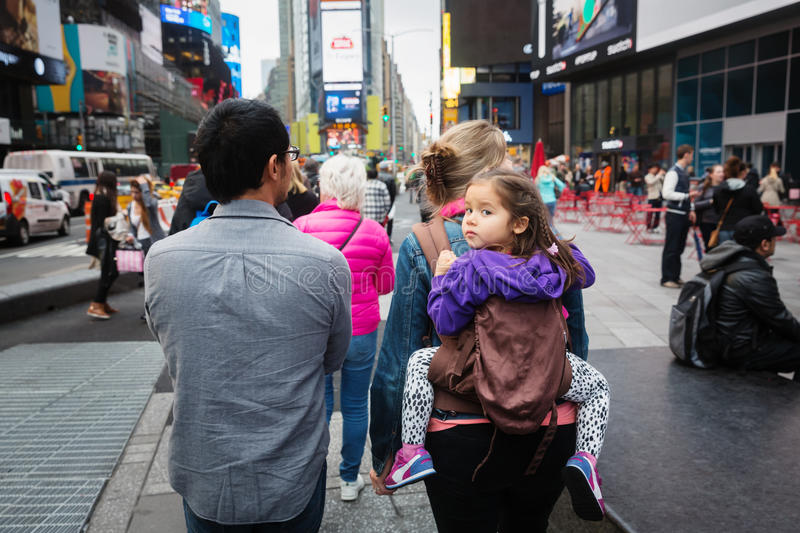 Manhattan street scene. NEW YORK, USA - May 03, 2016: Manhattan street scene. New Yorkers and tourists walking on Times Square in New York City. Young family stock photo