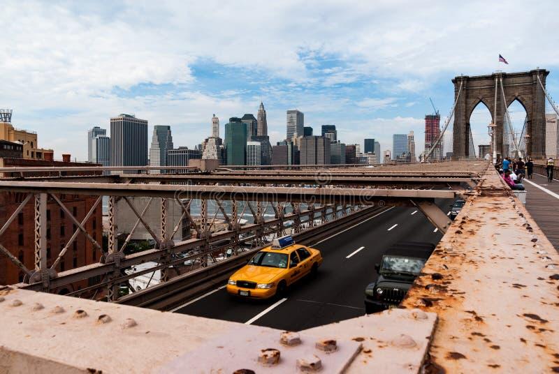 Manhattan van de Brug van Brooklyn, New York met gele taxi in de voorgrond stock afbeelding