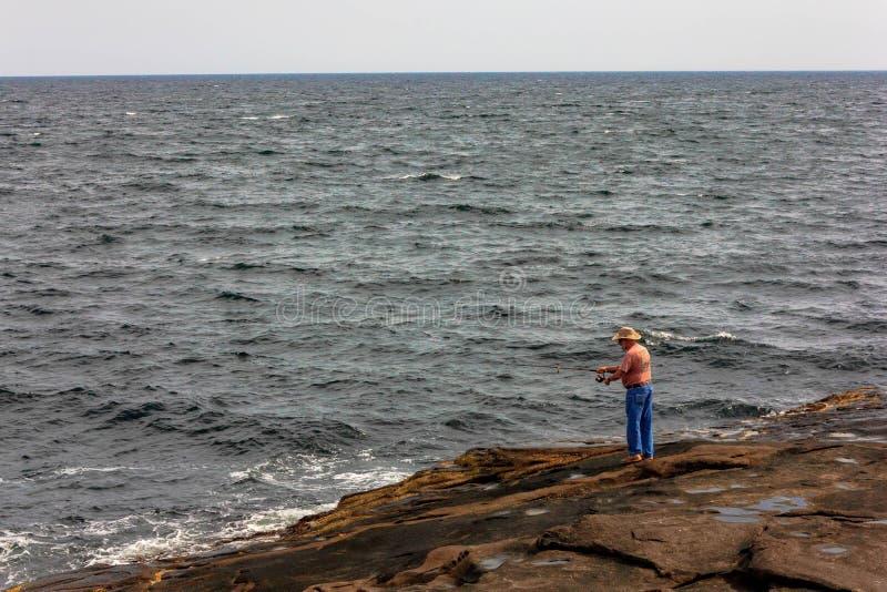Manhavet som fiskar av, vaggar på udde Neddick royaltyfri bild