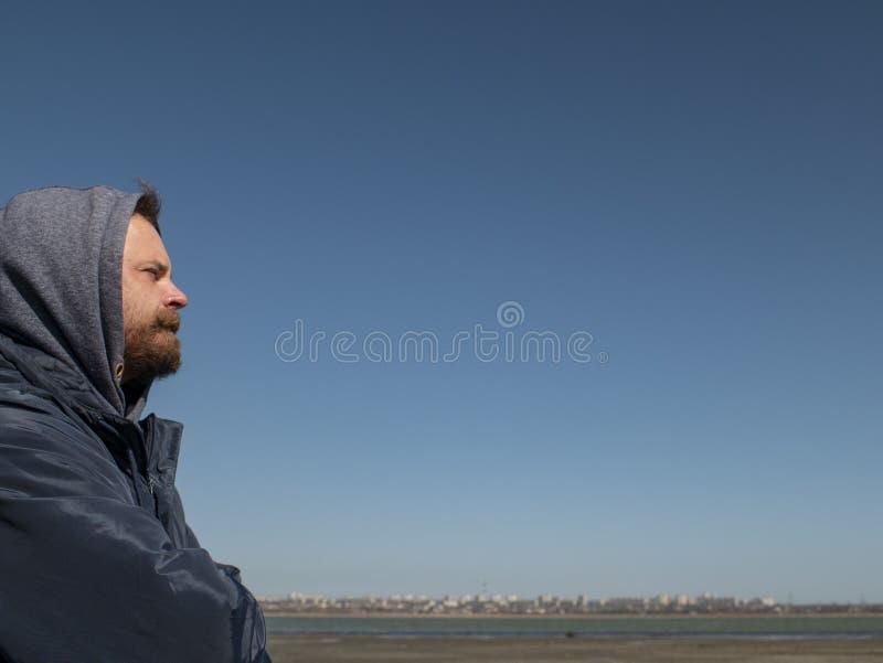 Manhipster med ett skägg och mustasch i huven mot den blåa himlen och breda flodmynningen royaltyfri foto