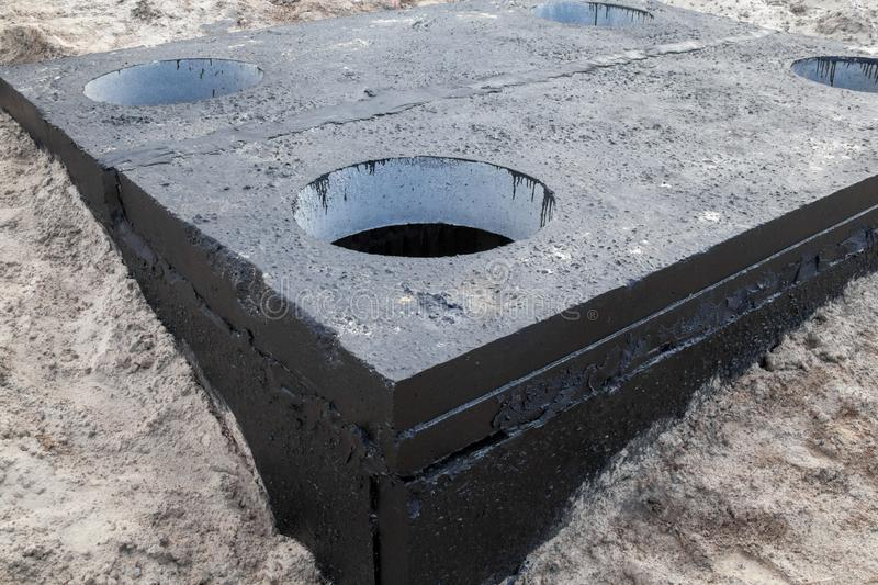 Manhole in the concrete block. Painted with black coal tar. Construction site stock image