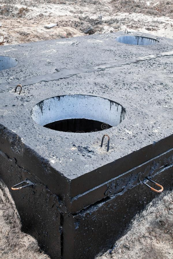 Manhole in the concrete block. Painted with black coal tar. Construction site royalty free stock photo