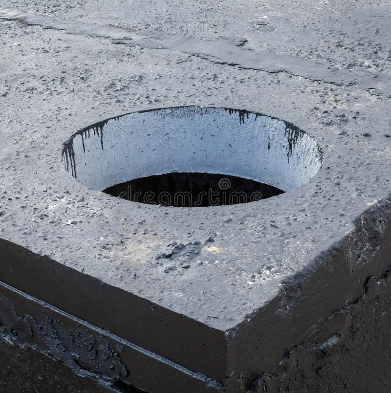 Manhole in the concrete block. Painted with black coal tar. Construction site royalty free stock photos