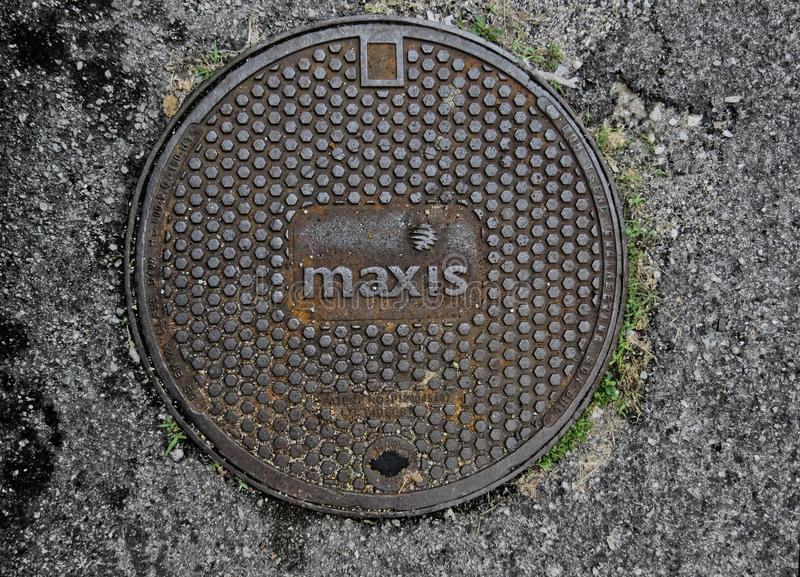 Manhole Cover Belonging To Maxis Berhad. Manhole cover belonging to Maxis Communications Malaysia Maxis Berhad with some rust stains, pebbles and gravel over it royalty free stock image