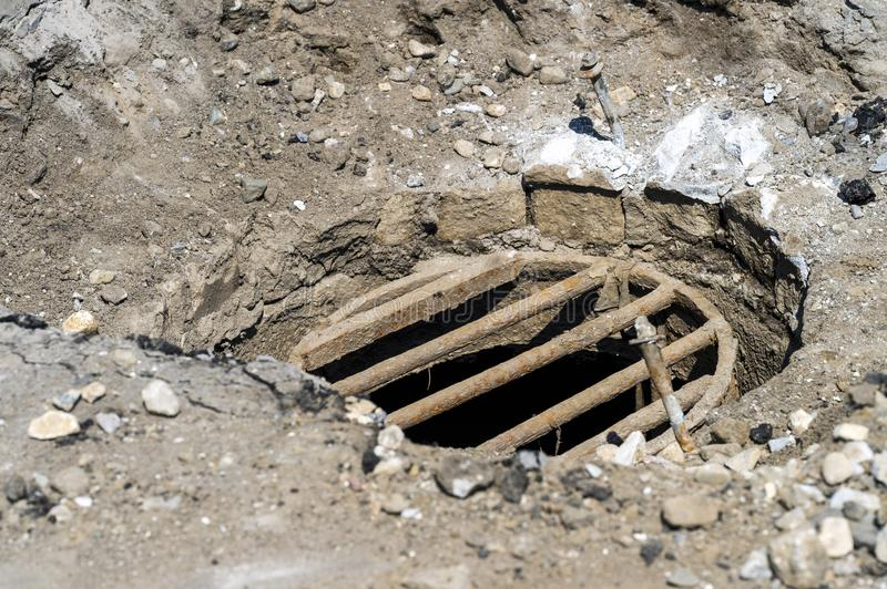 A manhole cover with grating. Sewer hatch with rusty dirty bars. Around the hatch dug earth and stones stock photography
