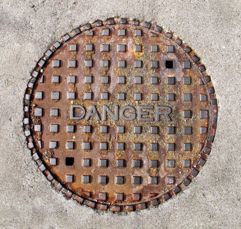 Free Manhole Cover Saying Danger Isolated Stock Photos - 23843363
