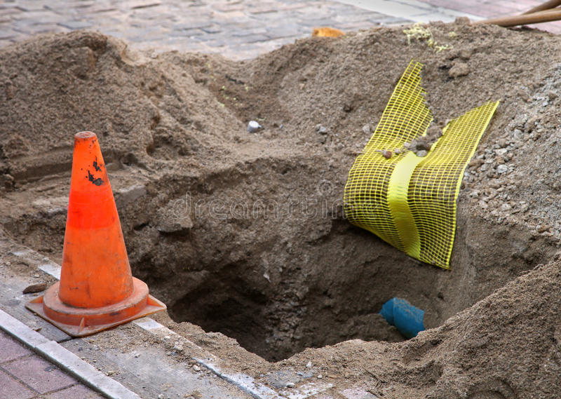 Manhole. Hole dug out for placing optic fibres royalty free stock image