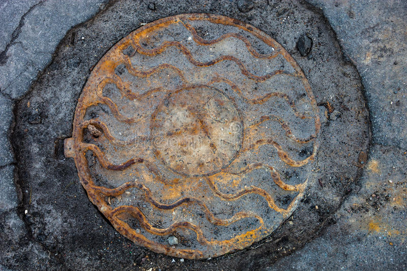 Manhole with rusty metal cover in cracked asphalt surface stock photos