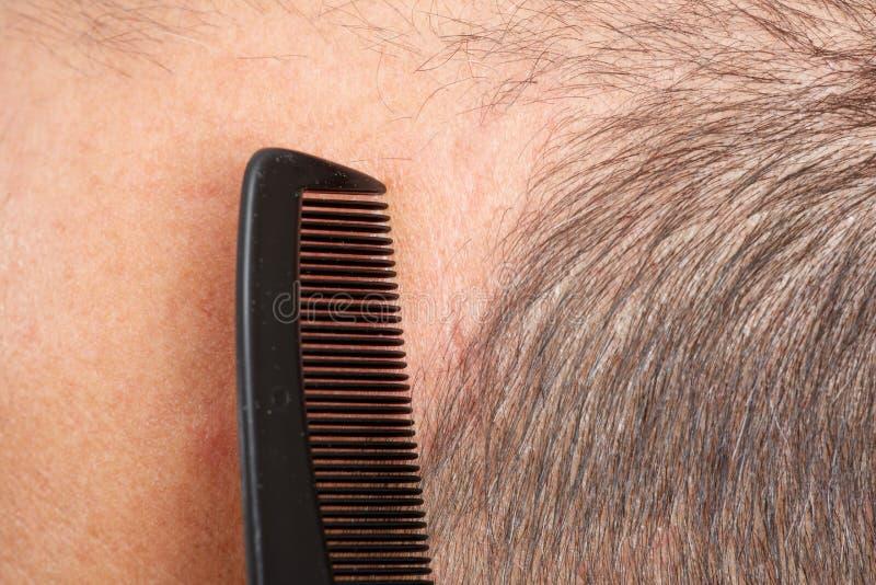 Manhuvud med en hårkam arkivfoto