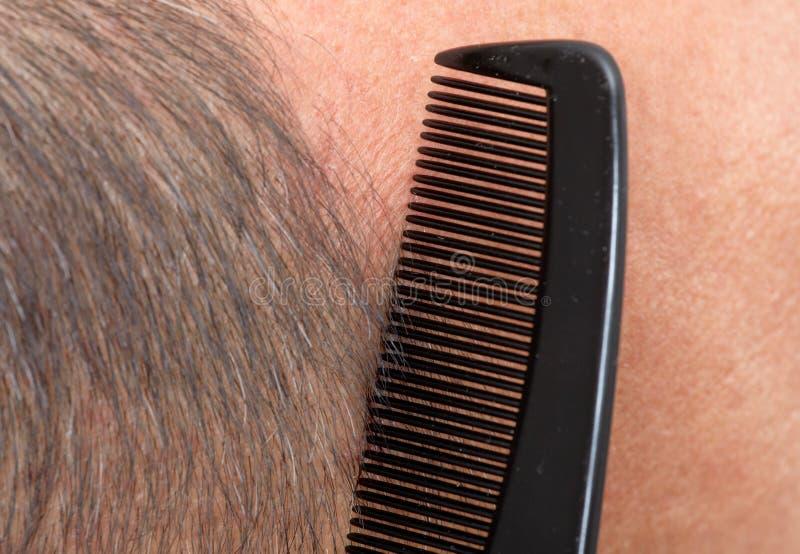 Manhuvud med en hårkam arkivbilder