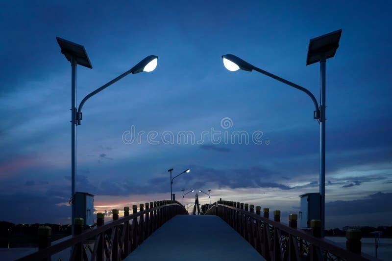Manière de chemin d'éclairage jusqu'au pont contre le coucher du soleil de ciel dans la soirée images stock