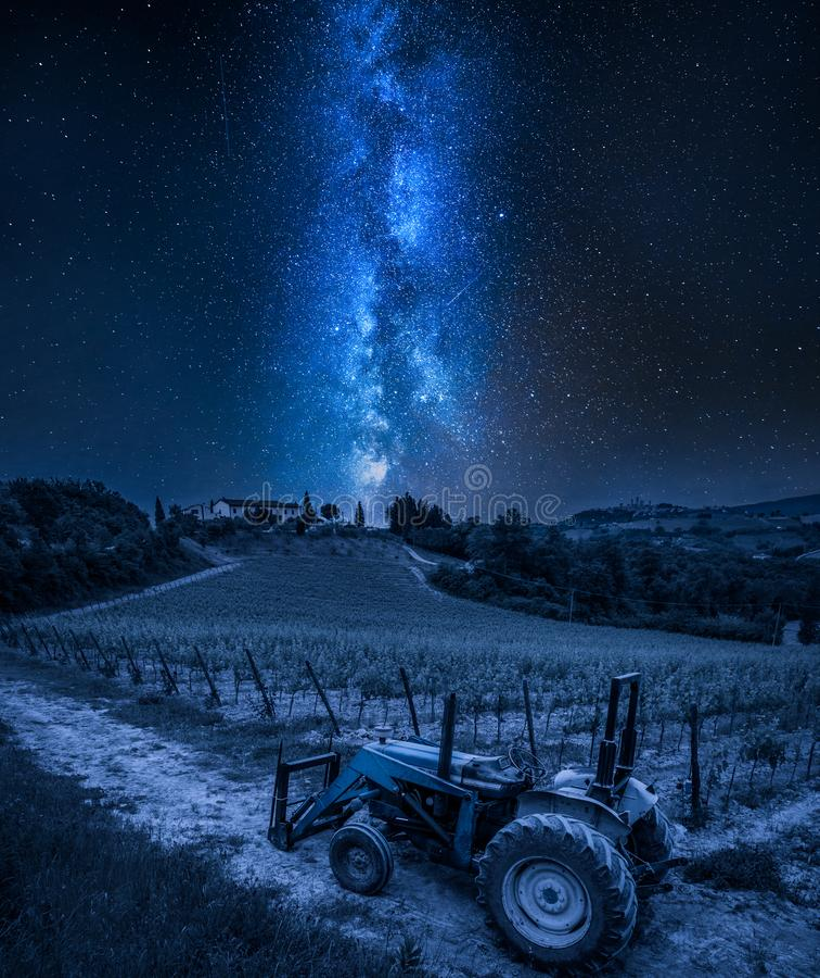 Manière laiteuse au-dessus des vignes et du vieux tracteur par nuit, Toscane photographie stock libre de droits