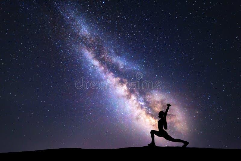 Manière laiteuse avec la silhouette d'un yoga de pratique de femme debout image stock